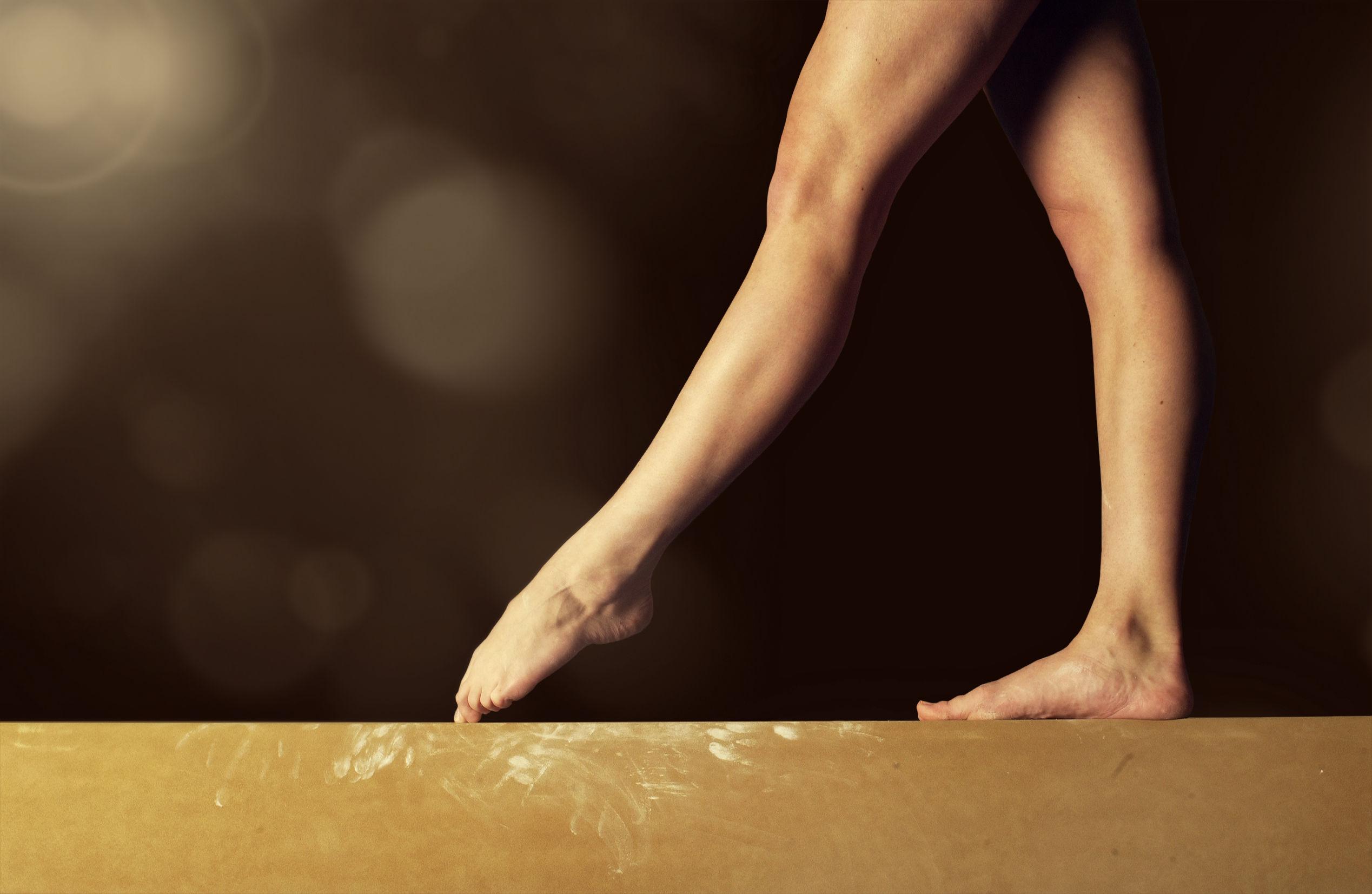 42133666 – close view of a gymnast legs on a balance beam