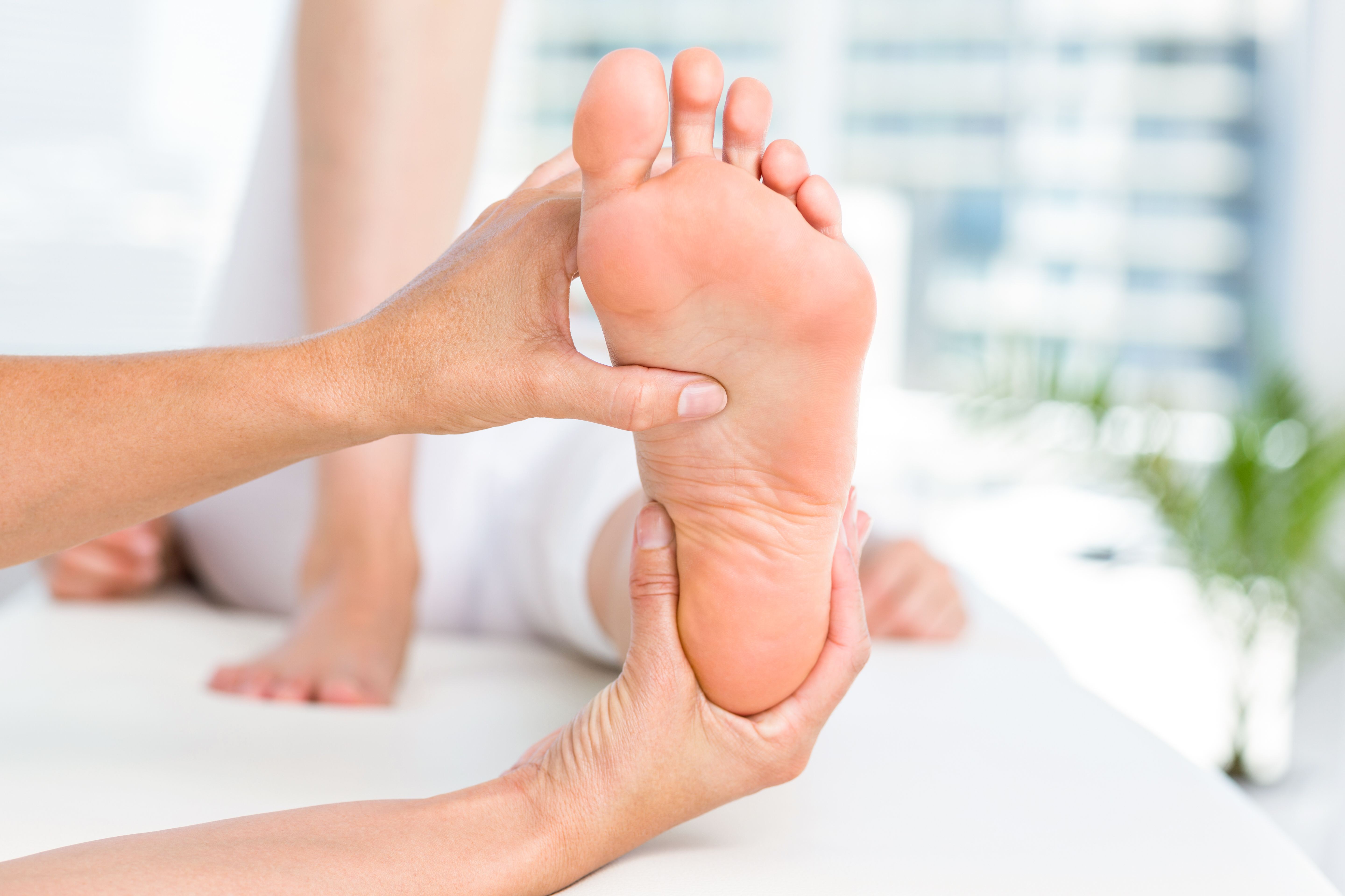Physiotherapist massaging her patients foot